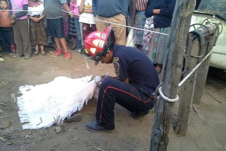 Socorrista cubre con una manta el cuerpo sin vida de Rosa Nohemí Noj Mejía, de 1 año y 6 meses, quien murió ahogada luego de haber caído en pozo artesanal. (Foto Prensa Libre: Cortesía de los Bomberos Municipales Departamentales)