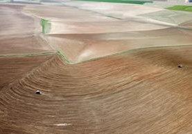 Fotografía aérea tomada desde un dron que muestra a unos agricultores mientras trabajan la tierra con sus tractores en Konya, Turquía. (Foto Prensa Libre: EFE)