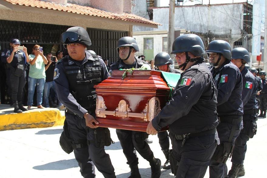 Colegas llevan en brazos los restos del jefe de la Policía de Guerrero, México, quien habría sido asesinado por su propio hijo. (Foto Prensa Libre: AP).