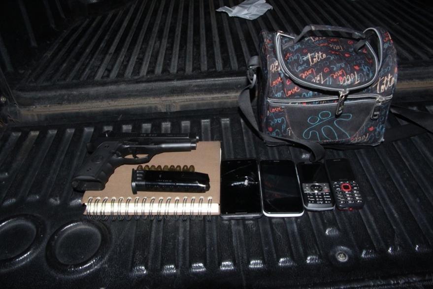 Un arma de fuego, municiones y teléfonos celulares fueron incautados al grupo. (Foto Prensa Libre: PNC)