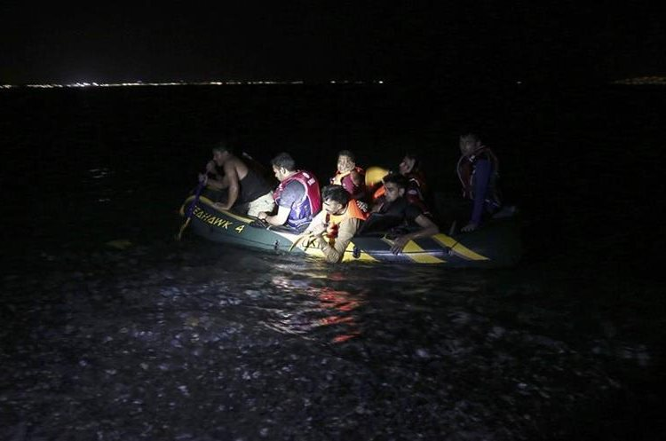 Migrants arrive on a dinghy at a coast after crossing from Turkey, at the southeastern island of Kos, Greece, Tuesday, Aug. 11, 2015. Fights broke out among migrants on the Greek island of Kos Tuesday, where overwhelmed authorities are struggling to contain increasing numbers of people arriving clandestinely on rubber dinghies from the nearby Turkish shore.  (AP Photo/Yorgos Karahalis)