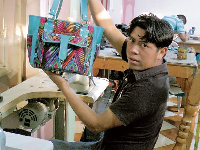 Francisco Cumes muestra una de las carteras  con mayor demanda en el mercado.(Foto Prensa Libre: Ángel Julajuj)