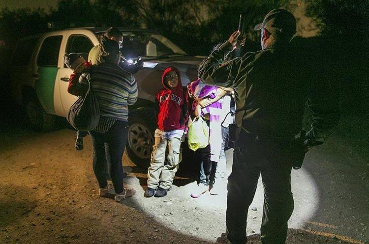 Indocumentados cons sus hijos sus hijos se preparan para ser trasladados por elServicios de inmigración en el Río Grande cerca de McAllen, Texas.(AP).