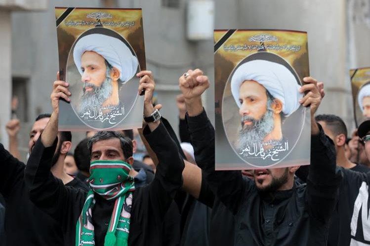 Chiíes saudíes sostienen pancartas con retratos del prominente clérigo musulmán chií Nimr al- Nimr durante la protesta. (Foto Prensa Libre: AFP).