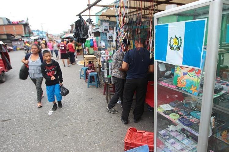 Vendedores del mercado de Jocotales, Chinautla, retomaron sus actividades comerciales. Algunos de los locatarios colocaron una bandera para indicar que ya han pagado la extorsión.&nbsp;(Foro Prensa Libre: Álvaro Interiano)<br />