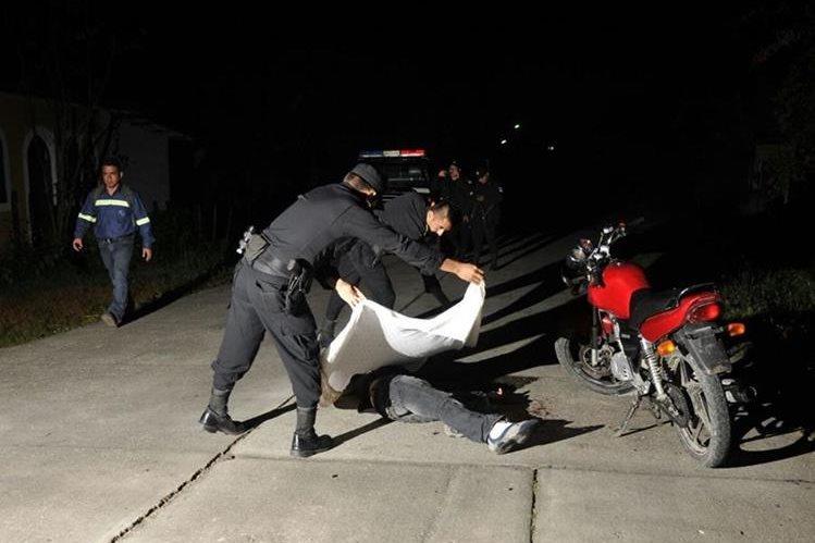 Agentes policiales cubren el cuerpo de Luis Emilio Chocooj Tiul. (Foto Prensa Libre: Rigoberto Escobar)
