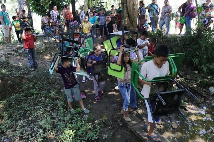 Los niños de la comunidad Nueva Esperanza cargan con sus escritorios para recibir sus clases en el terreno, donde se construirá el edificio. (Foto Prensa Libre: Dony Stewart)