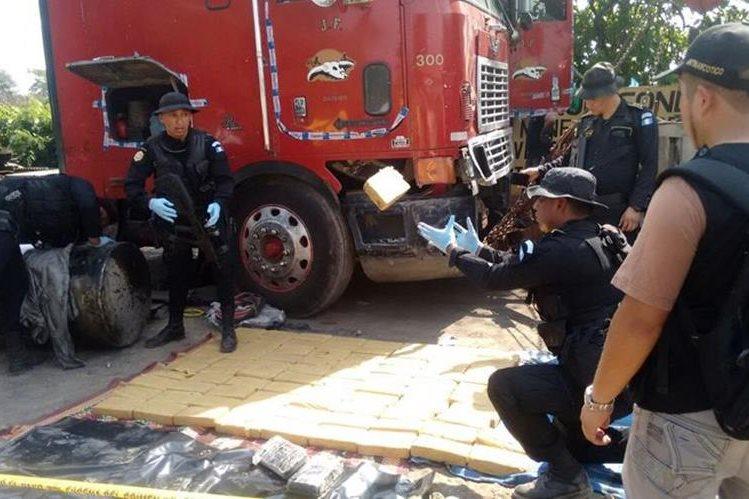 Agentes antinarcóticos extraen paquetes con droga hallados en tráiler, en la cabecera de Retalhuleu. (Foto Prensa Libre)