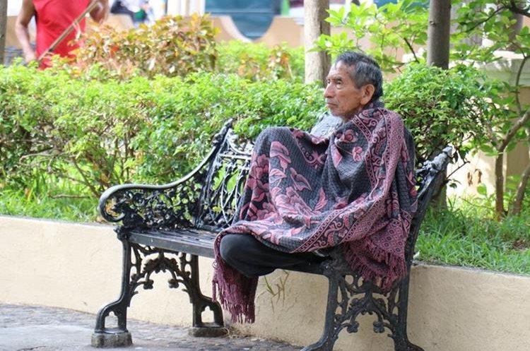 Un adulto mayor se abriga con una sábana en el parque Ismael Cerna de Chiquimula. (Foto Prensa Libre: Mario Morales)