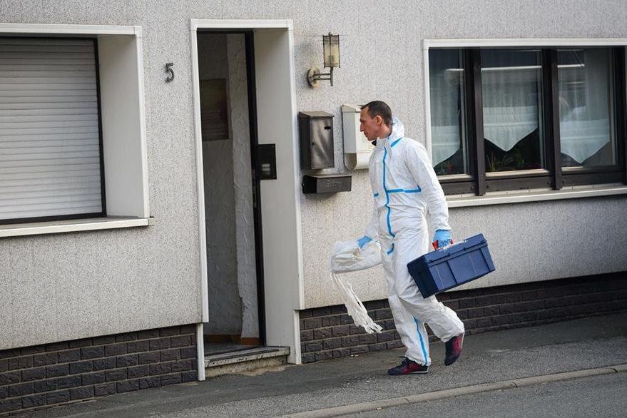 Un especialista en escenas del crimen ingresa a la vivienda donde ocurrió el hallazgo. (Foto Prensa Libre: AFP).