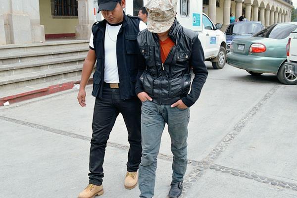 Agente de la Policía custodia a presunto extorsionista, en la ciudad de Quetzaltenango. (Foto Prensa Libre: Alejandra Martínez)