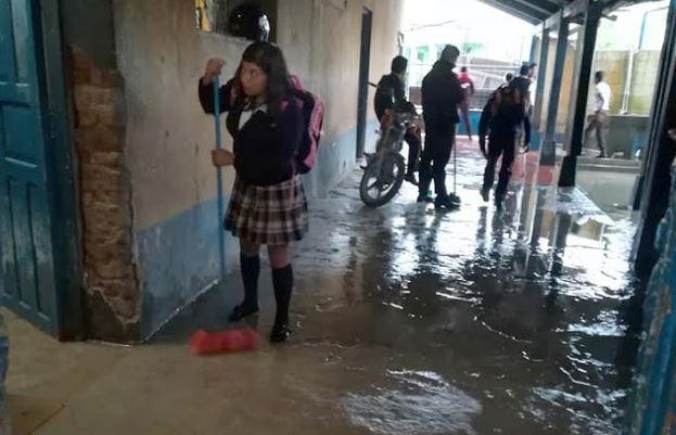 Una estudiante saca parte del agua que inundó la escuela en Chiantla, Huehuetenango. (Foto Prensa Libre: Mike Castillo)