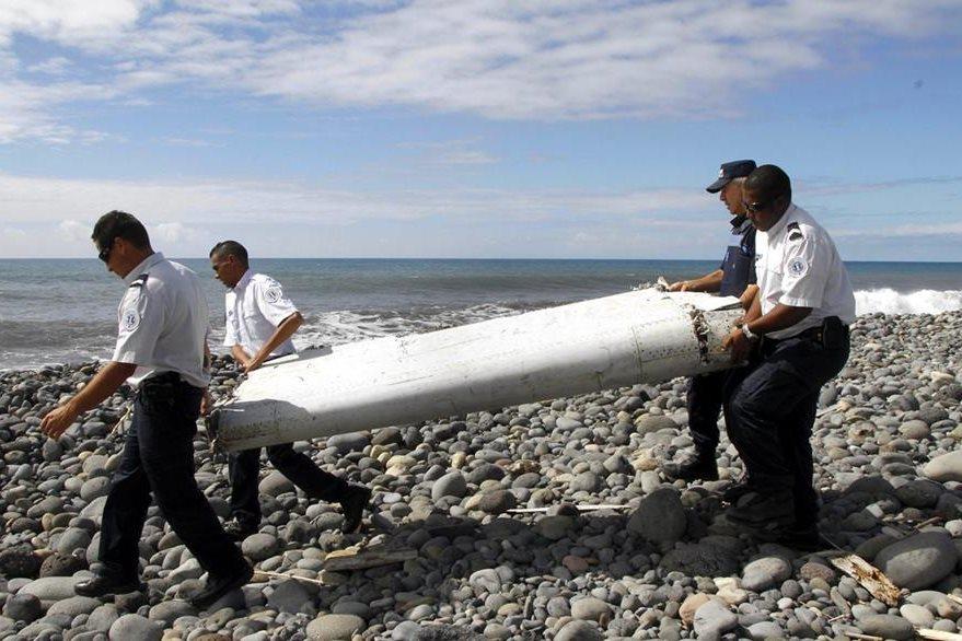 Oficiales de la Policía francesa en La Reunión trasladan el alerón del avión hallado en ese lugar. (Foto Prensa Libre: EFE).