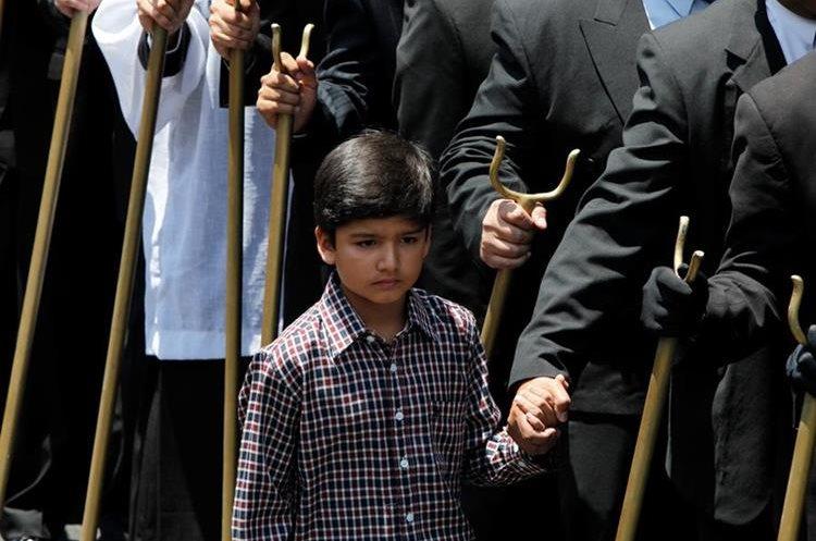 Un niño acompaña a su padre mientras carga en la procesión de Jesús Nazareno del Rescate. (Foto Prensa Libre: Paulo Raquec)