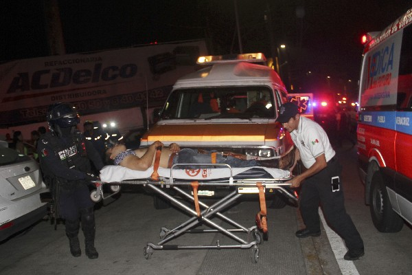 Paramédicos auxilian a un herido a después de una balacera en Xalapa,Veracruz.(EFE).