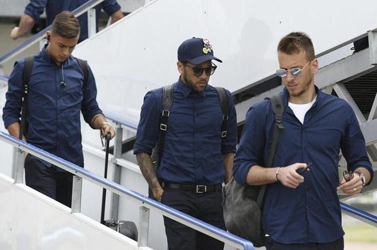Fotografía cedida por la UEFA que muestra la llegada del delantero argentino de la Juventus, Paulo Dybala (i) y el defensa brasileño Dani Alves (c) junto al resto del equipo al aeropuerto de Cardiff, Reino Unido. (Foto Prensa Libre: EFE)