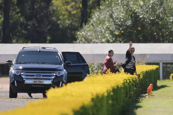 Dilma Rousseeff saluda a sus partidarios frente a la residencia presidencial.(AP).