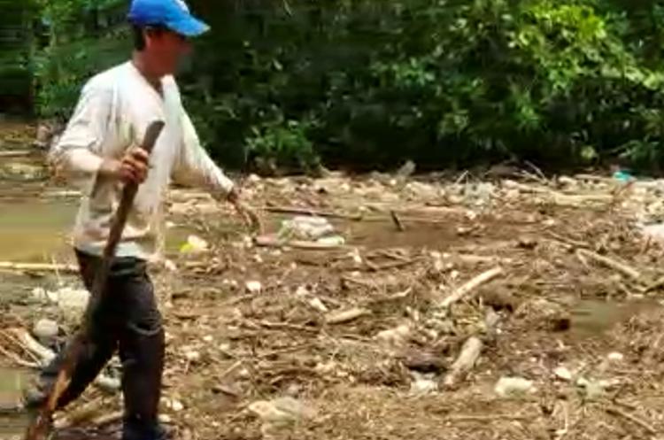 Un vecino de Tres Cruces, Retalhuleu, camina entre los desechos acumulados en el río Ocosito. (Foto Prensa Libre: Cortesía Joel Archila)