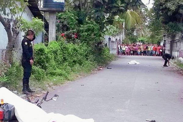Los cadáveres  de los dos hombres  quedaron sobre  la cinta asfáltica, en el barrio El Peñate, Puerto San José, Escuintla. (Foto Prensa Libre: Carlos Enrique Paredes)