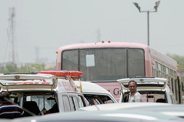 Un grupo paquistaníes están cerca del autobús que fue ataque por hombres armados en Karachi. (Foto Prensa Libre:AFP)