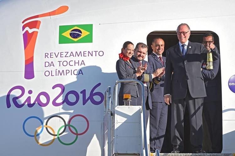 El presidente del Comité Olímpico Brasileño, Carlos Arthur Nusmann, muestra el fuego olímpico desde la puerta del avión luego de aterrizar este martes en la capital brasileña. (Foto Prensa Libre:AFP)
