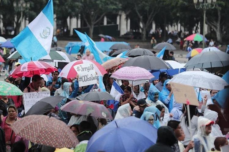 Sombrillas y manderas acompañan la manifestación. (Foto Prensa Libre: Juan Diego González)