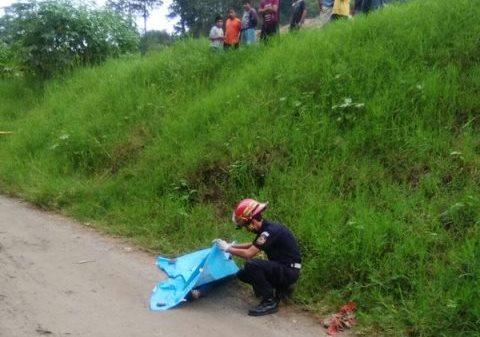 Un bombero inspecciona el cadáver de la fémina atacada en la ruta a Chinautla. (Foto Prensa Libre: CBM)