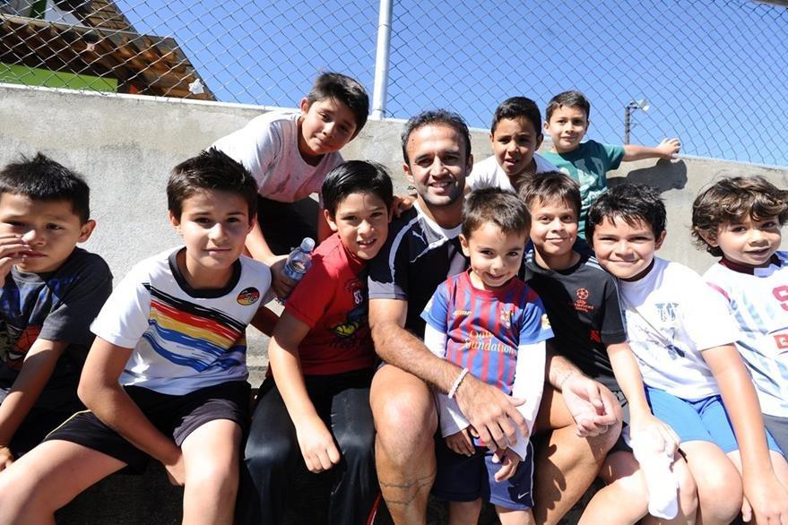 Contreras sonríe mientras posa con un grupo de niños al final del entrenamiento de Comunicaciones en Futeca Cayalá. (Foto Prensa Libre: Francisco Sánchez)