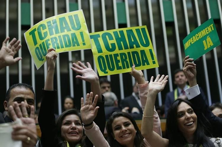 """Opposition lawmakers hold signs that read in Portuguese """"Goodbye dear"""" and """"Impeachment now"""" during a debate on whether or not to impeachment President Dilma Rousseff in the Chamber of Deputies in Brasilia, Brazil, Saturday, April 16, 2016. Sunday"""