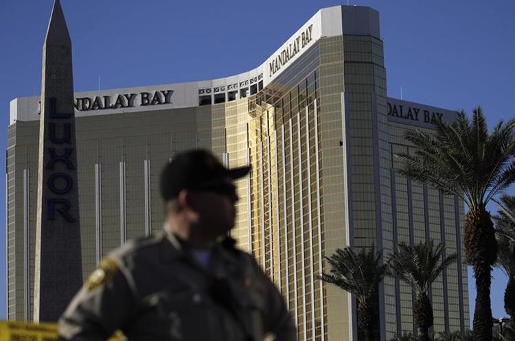 FILE - In this Tuesday, Oct. 3, 2017 file photo, a Las Vegas police officer stands by a blocked off area near the Mandalay Bay casino in Las Vegas. On Sunday, Oct. 1, Stephen Paddock opened fire on the Route 91 Harvest Festival killing dozens and wounding hundreds.  Paddock spent hours in casinos. and was known for betting big on video poker and staring down fellow gamblers.  There is no indication, though, that any particular grievance set him off. But details that have surfaced so far about the one-time IRS agent and son of a notorious bank robber, are clues, at least, to his mindset.  (AP Photo/John Locher, File)