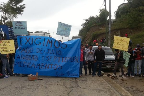 <p>Con mantas y barreras humanas, salubristas bloquearon la ruta interamericana para exigir el pago de salarios atrasados. (Foto Prensa Libre: Mike Castillo).</p>