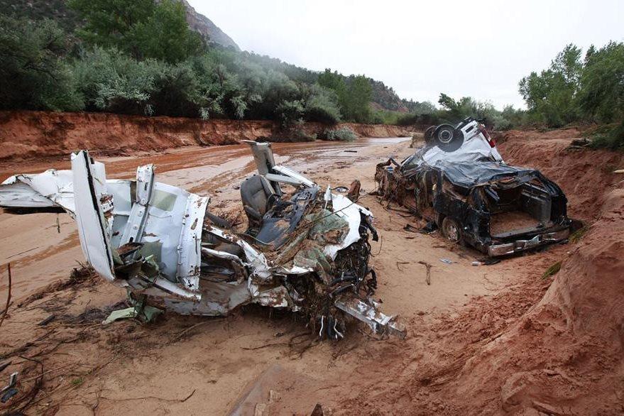 Dos vehículos destruidos por la inundación en los que viajaban un total de 16 mujeres y niños.
