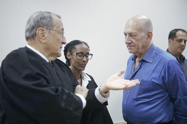 El ex primer ministro israelí Ehud Olmert (dcha) conversa con sus abogados en los juzgados en Jerusalén, Israel. (Foto Prensa Libre:EFE)