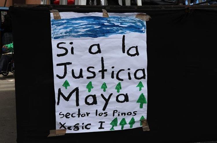 Un cartel que llevaba un comunitario muestra el respaldo a esa medida. (Foto Prensa Libre: Héctor Cordero)