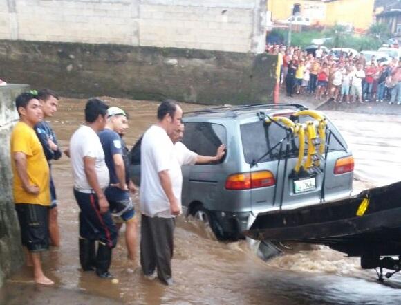 Vecinos y Bomberos Voluntarios auxiliaron a la familia que fue arrastrada por el río en Cuyotenango, Suchitepéquez. (Foto Prensa Libre: Cristian I. Soto)