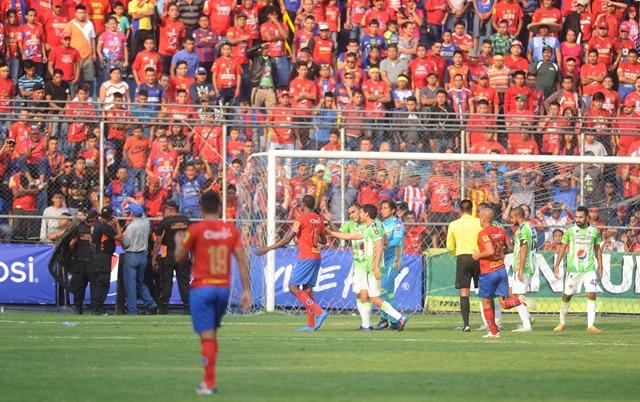 Víctor Bolívar reclama al árbitro López y jugadores rojos por los objetos lanzados al campo por la afición. (Foto Francisco Sánchez).