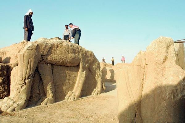 Trabajadores iraquíes  limpian una estatua en un sitio arqueólógico de Nimrud. (Foto Prensa Libre: AFP)