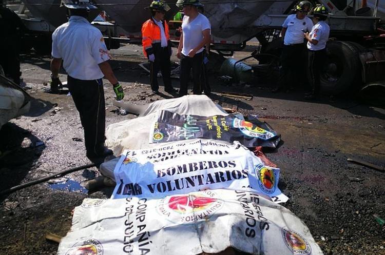Bomberos observan los cuerpos de varias personas que perdieron sus vidas en el accidente