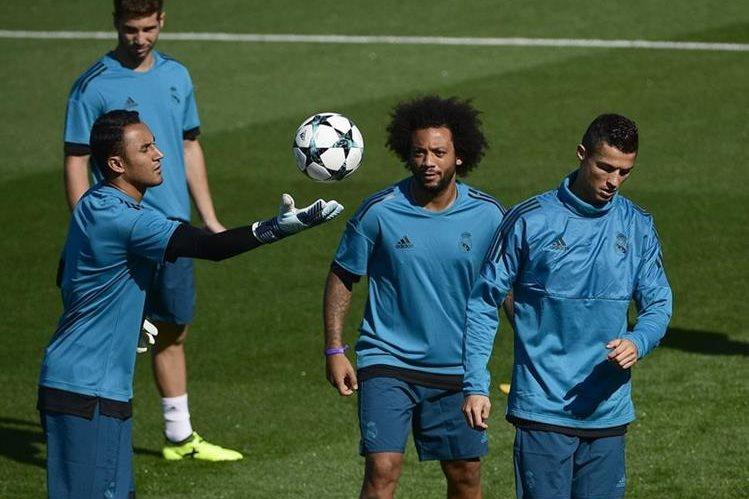 Keylor Navas sostiene el balón mientras es observado por Marcelo y Cristiano Ronaldo en la última practica del Real Madrid antes de recibir al Apoel en la Champions League. (Foto Prensa Libre: AFP)