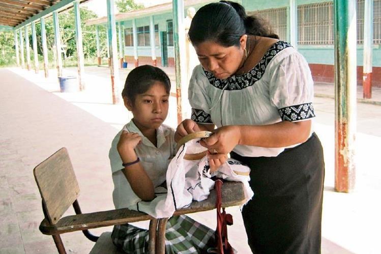 La maestra mopán, Aurelia Pop Chun, enseña sobre tejidos de esta cultura a estudiante de una escuela de San Luis, Petén.