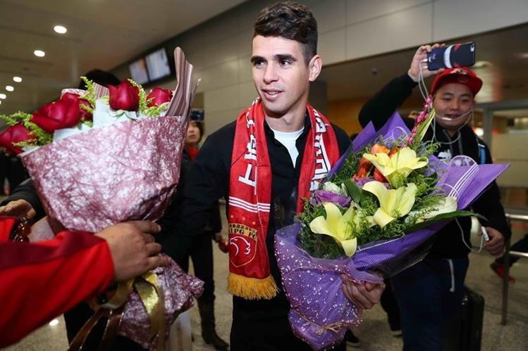 El futbolista brasileño Oscar es recibido por aficionados en el aeropuerto Pudong de Shanghai. (Foto Prensa Libre: AFP).