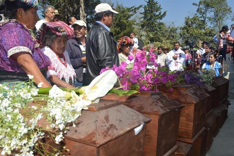 Pobladores observan algunos de los ataúdes que contienen los restos de las víctimas del conflicto armado en Uspantán. (Foto Prensa Libre: Óscar Figueroa).