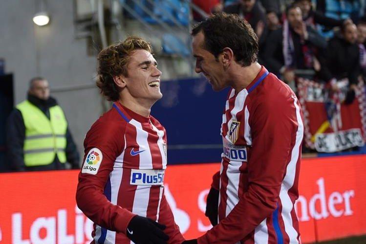 Griezmann celebra con su compañero de equipo Diego Godín luego de anotar un gol. (Foto Prensa Libre: AFP)