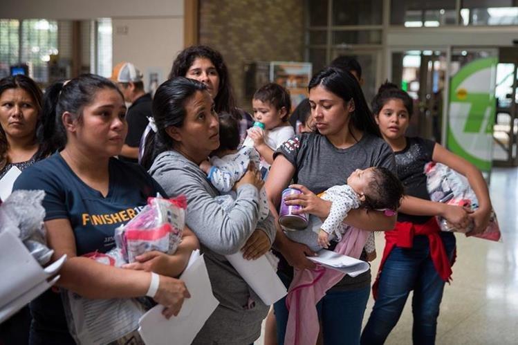 Madres inmigrantes con sus hijos caminan a un centro de socorro cercano de Catholic Charities, en McAllen, Texas. (Foto Prensa Libre: AFP)