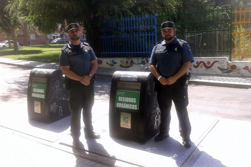 Los dos agentes junto al contenedor de basura al que habia sido arrojado un bebé en Mejorada del Campo. (Foto Prensa Libre: EFE).