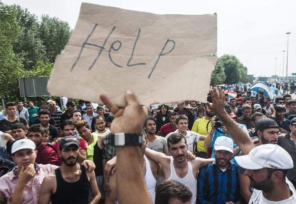 """Un refugiado porta una pancarta en la que se puede leer """"Ayuda"""" en la frontera con Hungría."""