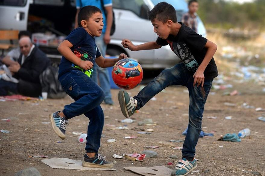 Niños inmigrantes juegan fútbol mientras esperan la autorización para abordar un tren y cruzar la frontera entre Macedonia y Grecia. (Foto Prensa Libre: EFE).