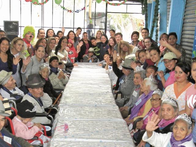 Ancianos disfrutan, junto a voluntarios, un momento de alegría, durante la convivencia organizada por las fiestas de fin de año en el asilo San José.