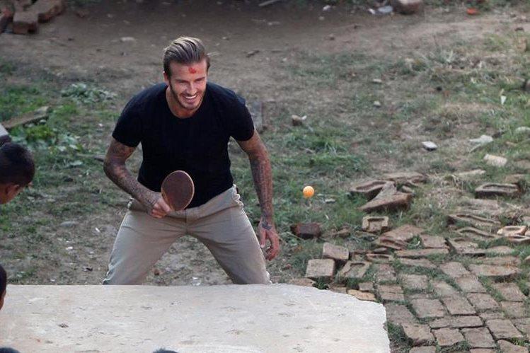 El excapitán de Inglaterra, jugó con niños de un barrio pobre en Argentina. (Foto Prensa Libre: AFP)