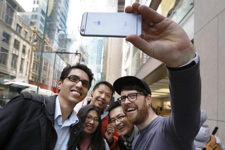 Un empleado de Apple posa para un selfi con varios clientes con un iPhone 6S, en Australia. (PL-EFE)